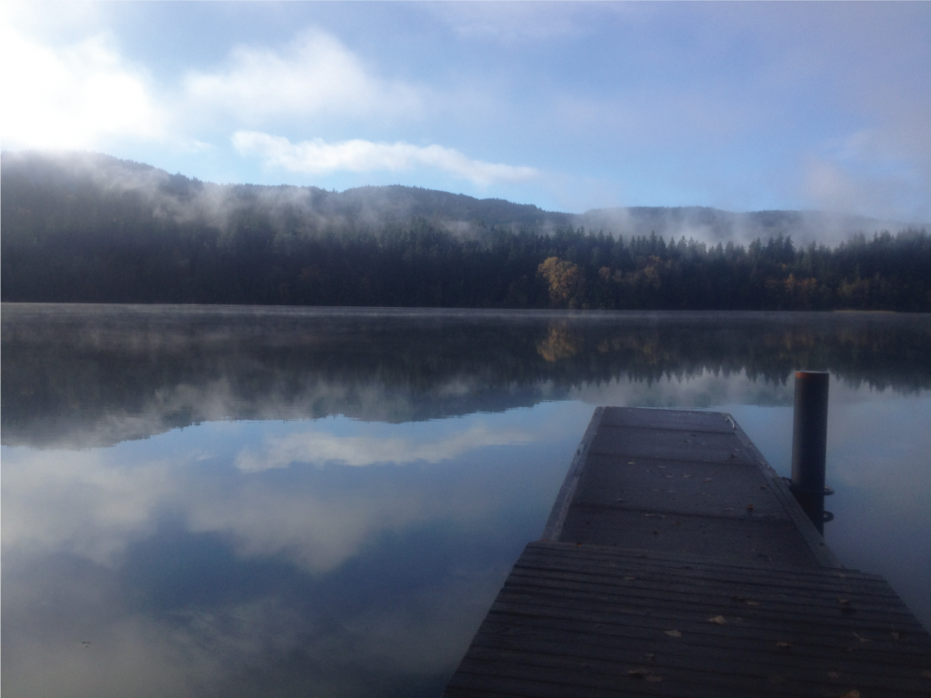 The dock over placid Lake Padden, with clouds reflected in the water's surface.